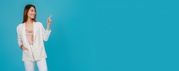 Mulher de negócios asiática bonita blogueira com postura com a mão. comprimento total em pé isolado na parede azul