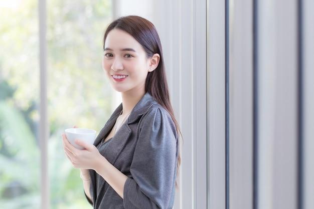 Mulher de negócios asiática bonita em pé segurando a xícara de café perto da janela alegremente no local de trabalho
