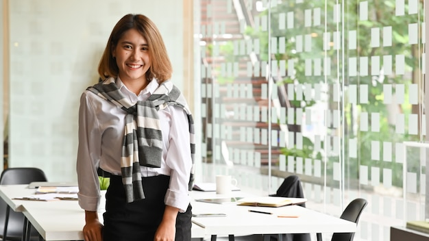 Mulher de negócios asiática bonita que sorri confiàvel no quarto de reunião.