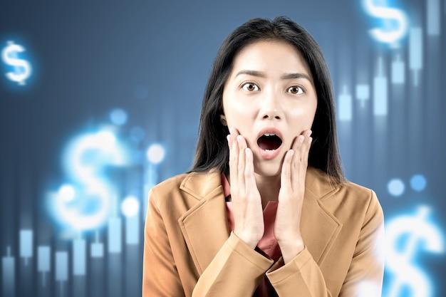 Mulher de negócios asiática chocada olhando gráfico de barras virtual de dólar com fundo digital