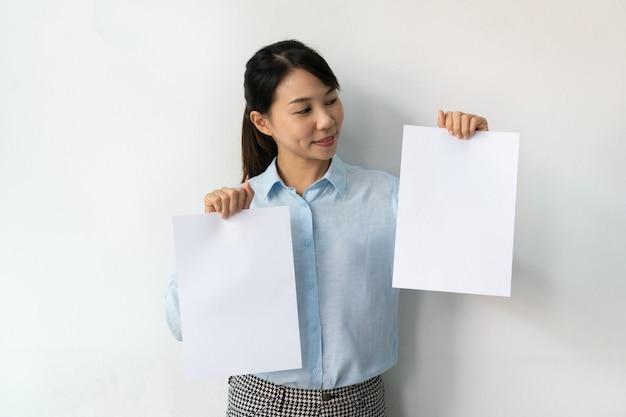 Mulher de negócios asiática com camisa azul segura uma folha de papel em branco nas mãos para propaganda