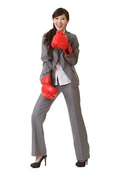 Mulher de negócios asiática com luvas de boxe vermelhas