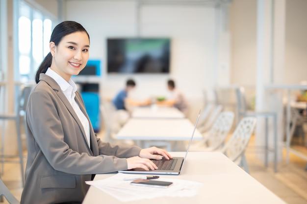 Mulher de negócios asiática com sucesso laptop pose feliz educação universitária de comércio eletrônico