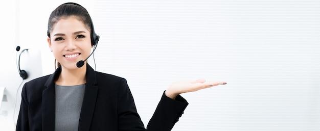 Mulher de negócios asiática como um operador em call center fazendo gesto de mão aberta (palma)