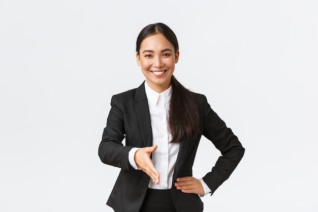 Mulher de negócios asiática confiante e sorridente estende a mão para um aperto de mão firme, cumprimentando o cliente ou parceiro de negócios para assinar o acordo, parecendo determinada e pronta, com fundo branco de pé