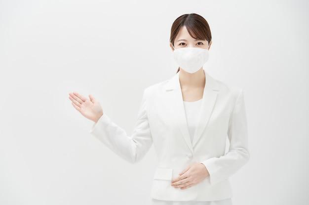 Mulher de negócios asiática de terno branco e máscara