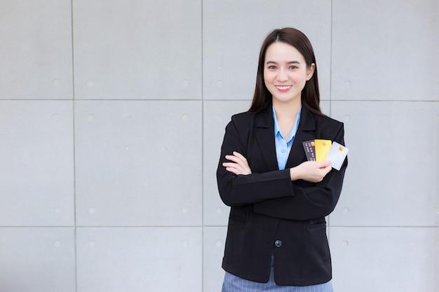Mulher de negócios asiática em terno preto formal segurando e mostrando o cartão de crédito na mão