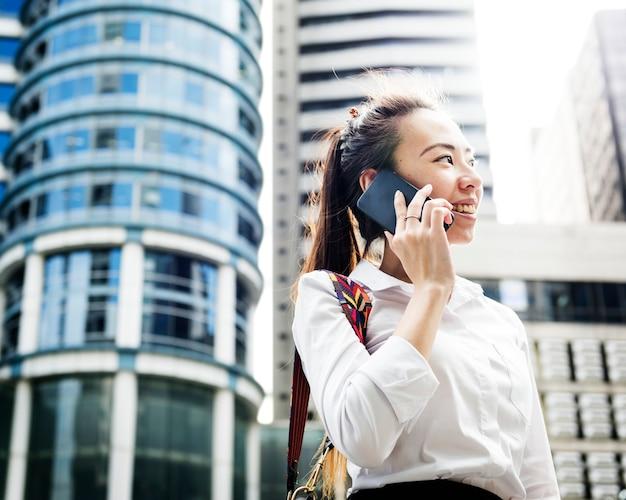 Mulher de negócios asiática em uma cidade ao telefone