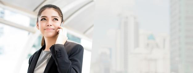 Mulher de negócios asiática falando em seu telefone celular fora do escritório.