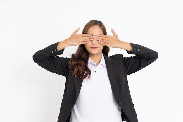 Mulher de negócios asiática fechando os olhos com as duas mãos