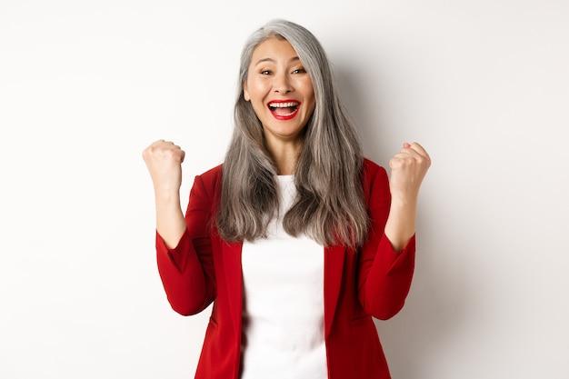 Mulher de negócios asiática feliz alcança o sucesso, ganhando o prêmio e comemorando, dizendo sim com os punhos erguidos, feliz contra um fundo branco