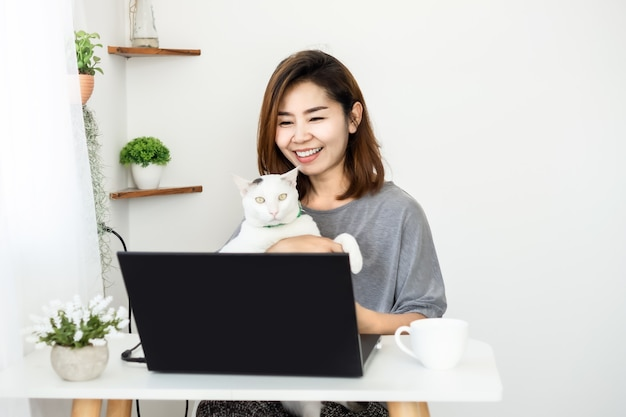 Mulher de negócios asiática feliz trabalhando em casa com um gato