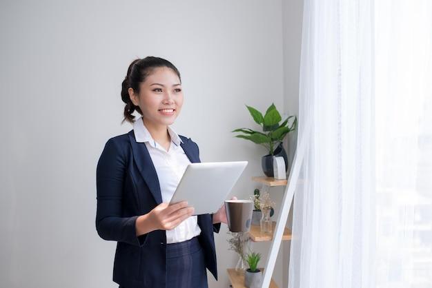 Mulher de negócios asiática, forte e confiante em pé no corredor de um prédio de escritórios, segurando um computador tablet