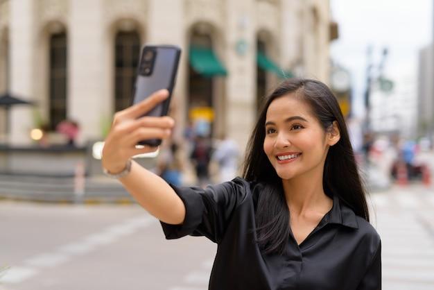 Mulher de negócios asiática influenciadora ao ar livre em uma rua da cidade usando um telefone celular enquanto faz um vlog ou tira uma selfie
