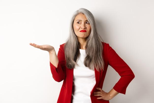 Mulher de negócios asiática irritada e confusa estendeu a mão para o lado e encolheu os ombros, olhando questionada para a esquerda, fundo branco