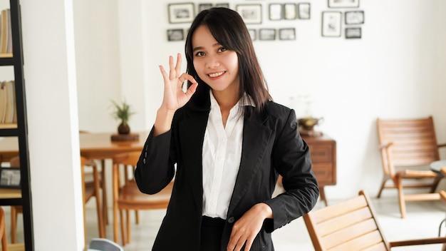 Mulher de negócios asiática jovem bonita de terno e dedo bem levantado no escritório