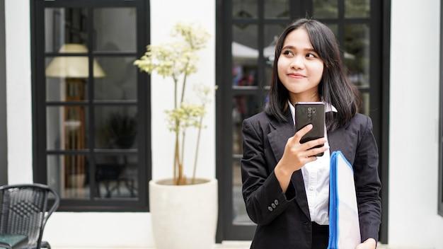 Mulher de negócios asiática jovem bonita em um terno de pé no café com telefone e envelope marrom