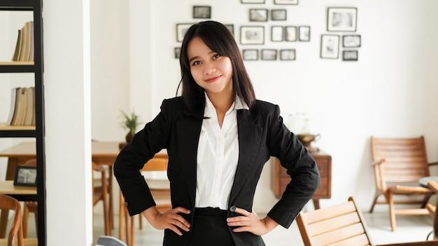Mulher de negócios asiática jovem bonita em um terno de pé no café