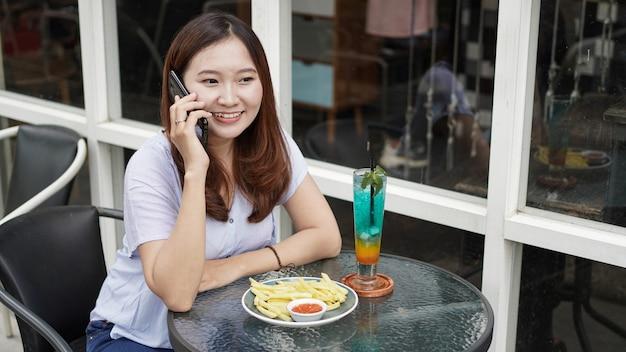 Mulher de negócios asiática ligando para um café