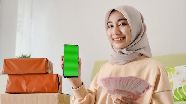 Mulher de negócios asiática mostrando a tela do smartphone