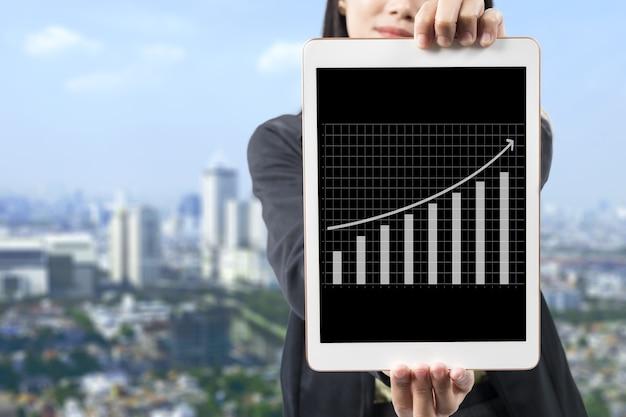 Mulher de negócios asiática mostrando gráfico de finanças de negócios na tela do tablet