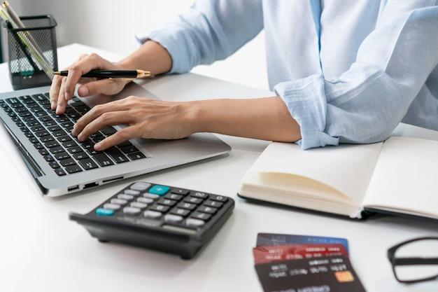Mulher de negócios asiática ocupada trabalhando em um laptop no escritório