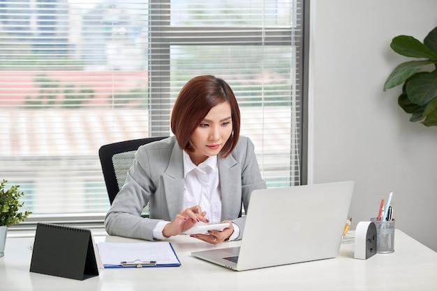 Mulher de negócios asiática ou contadora trabalhando apontando gráfico de discussão e análise de dados gráficos e gráficos e usando uma calculadora
