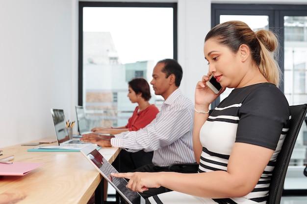 Mulher de negócios asiática positiva lendo um documento em um tablet ou navegando nas redes sociais ao ligar para o cliente