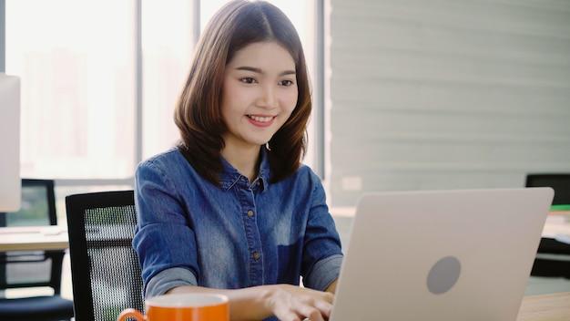 Mulher de negócios asiática profissional que trabalha em seu escritório através do portátil.