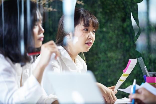 Mulher de negócios asiática que explica algo a seu colega