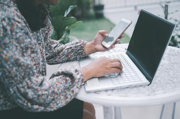 Mulher de negócios asiática que trabalha em casa se comunica com o escritório por videoconferência