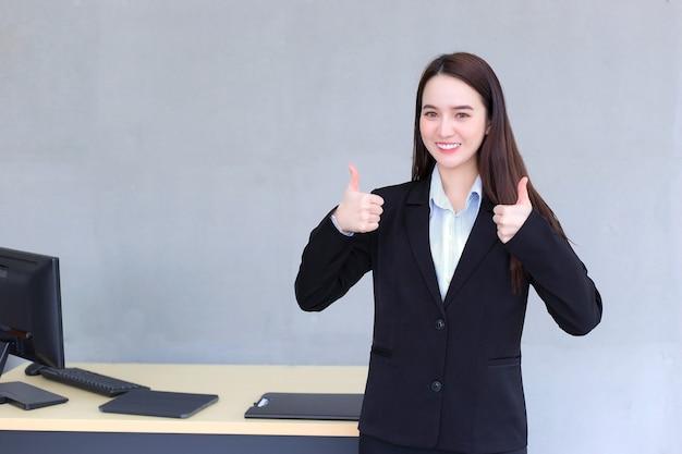 Mulher de negócios asiática que usa terno preto sorri e mostra a mão no ar como um bom sinal no escritório