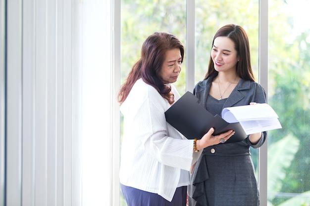 Mulher de negócios asiática se levanta e fala com outra para consultar atentamente sobre o trabalho no escritório.