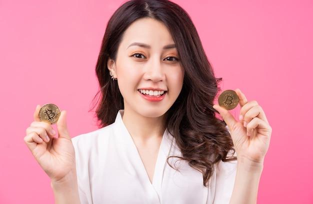 Mulher de negócios asiática segurando bitcoin na mão