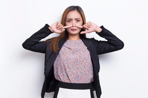 Mulher de negócios asiática segurando o nariz por causa de um cheiro ruim