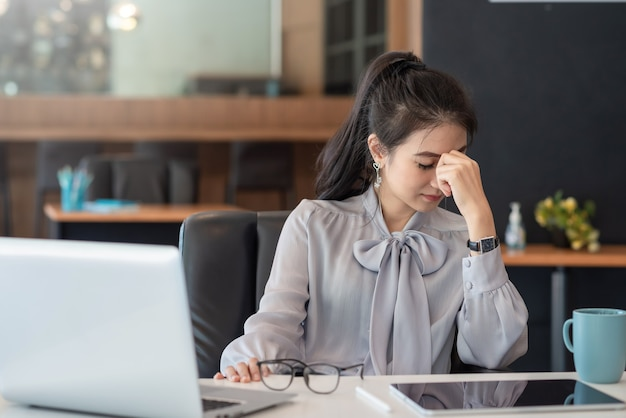 Mulher de negócios asiática sentada por muito tempo diante da tela do computador do trabalho, causando cansaço visual e sentindo-se estressada no escritório