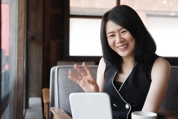 Mulher de negócios asiática sorridente é videochamada nas mídias sociais com tablet na cafeteria.