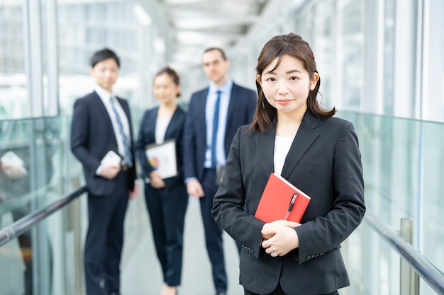 Mulher de negócios asiática sorridente em pé e sua equipe de negócios