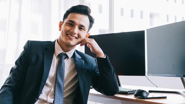 Mulher de negócios asiática sorrindo com confiança ao lado de duas telas de computador em branco