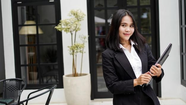 Mulher de negócios asiática sorrindo com um envelope pardo e parada na frente do escritório