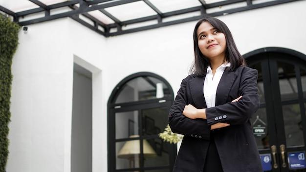 Mulher de negócios asiática sorrindo e parada na frente do escritório
