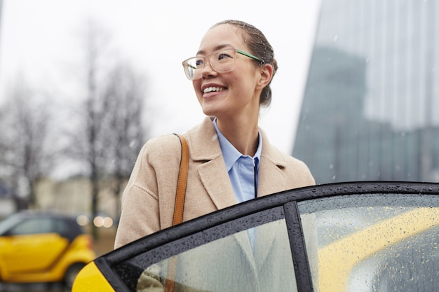 Mulher de negócios asiática taking taxi na rua chuvosa