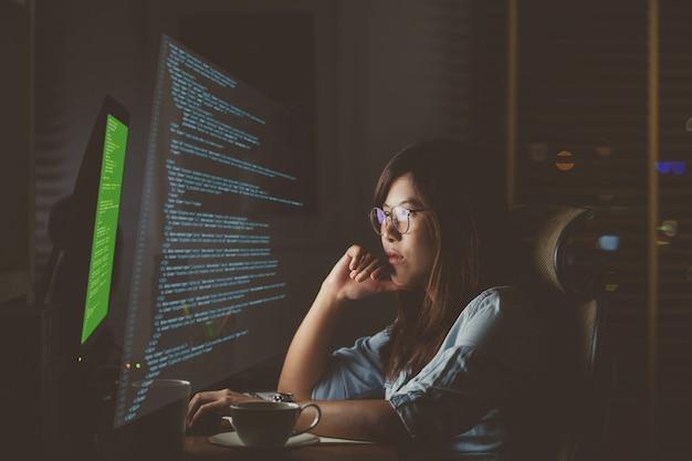 Mulher de negócios asiática trabalhando duro na frente da área de trabalho do computador com o código-fonte de programação