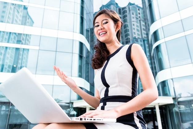 Mulher de negócios asiática trabalhando em um laptop em frente ao prédio da torre