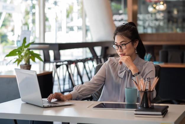Mulher de negócios asiática trabalhar com o laptop no escritório.