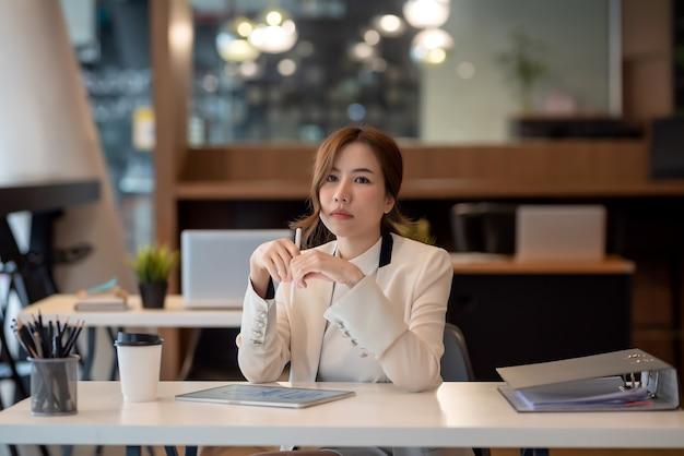 Mulher de negócios asiática usa ideias de trabalho com gráficos em tablets no escritório.