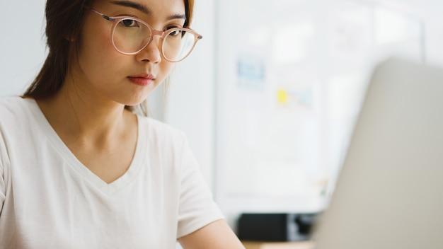 Mulher de negócios asiática usando laptop fala com colegas sobre o plano de videochamada enquanto trabalha em casa na sala de estar.