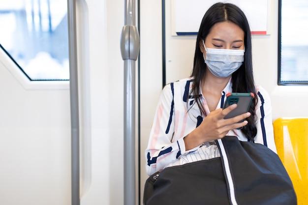 Mulher de negócios asiática usando máscaras durante a pandemia de covid-19 enquanto se deslocava de transporte público