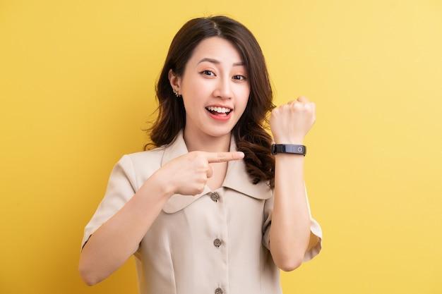 Mulher de negócios asiática usando smartband na mão para monitorar as calorias queimadas