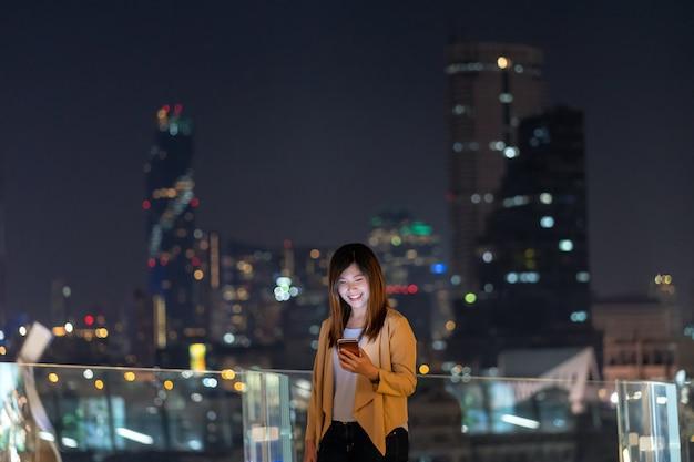 Mulher de negócios asiática usando telefone celular inteligente com ação de sorriso na área financeira